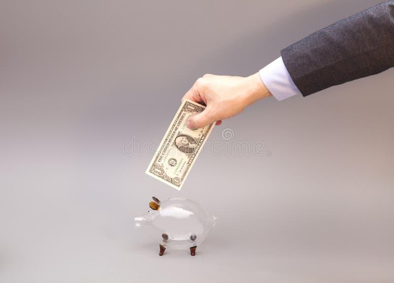 Mano masculina que pone un billete de dólar en la hucha de cristal imagen de archivo