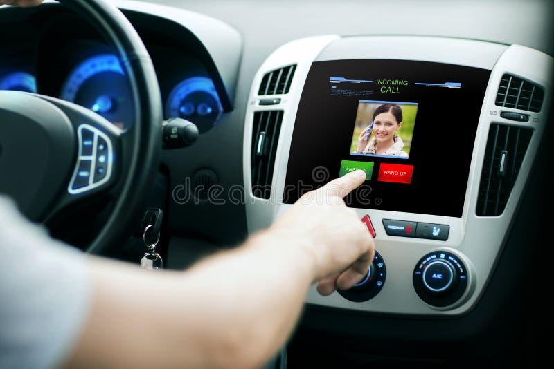 Mano masculina que recibe la llamada video en la pantalla del panel del coche fotografía de archivo