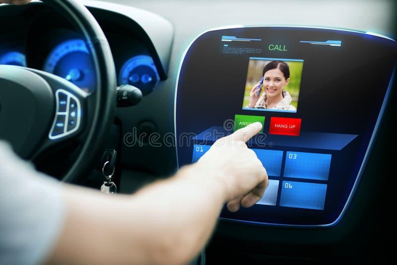 Mano masculina que recibe la llamada video en la pantalla del panel del coche imagen de archivo
