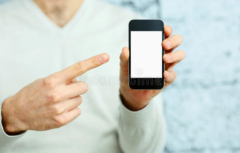 Mano masculina que señala en la exhibición del smartphone fotos de archivo