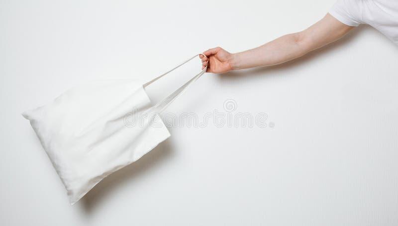 Mano masculina que sostiene el bolso blanco de la materia textil imagen de archivo