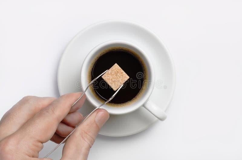 Mano masculina que sostiene las pinzas del azúcar con el cubo del azúcar de caña sobre la taza de café sólo contra la opinión sup imagen de archivo libre de regalías