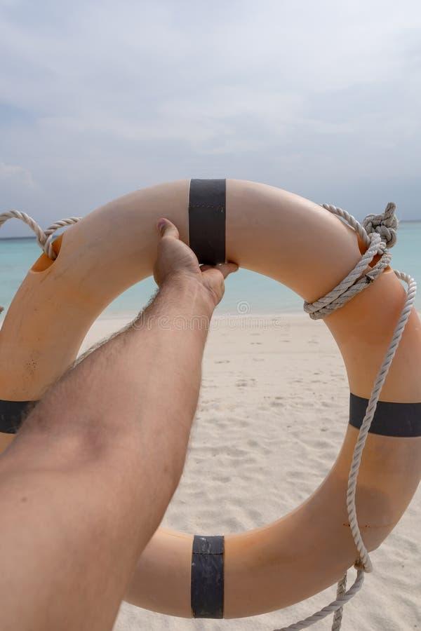 Mano masculina que sostiene un conservante de vida En la arena, el mar y el cielo del fondo imágenes de archivo libres de regalías