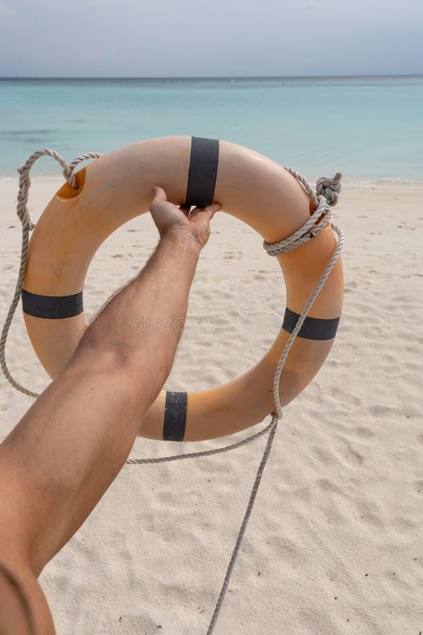 Mano masculina que sostiene un conservante de vida En la arena, el mar y el cielo del fondo imagen de archivo libre de regalías
