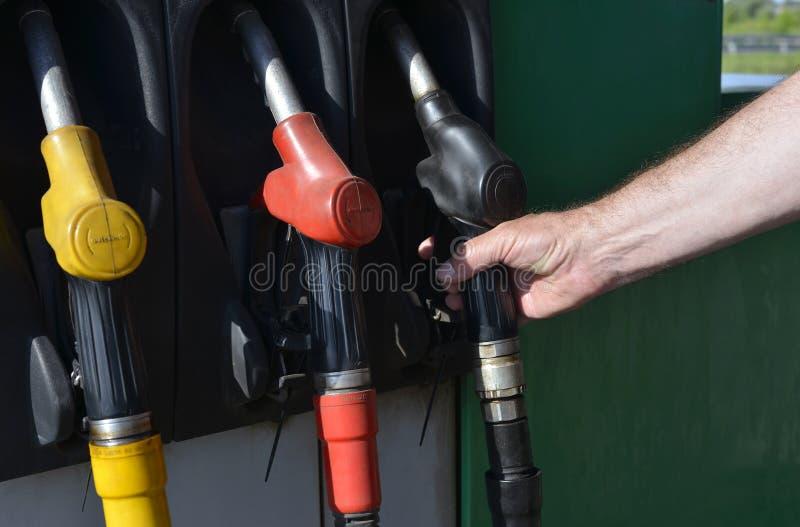 Mano masculina que sostiene un surtidor de gasolina imágenes de archivo libres de regalías