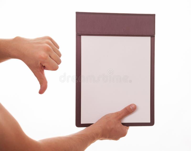 Mano masculina que sostiene un tablero con la hoja de papel vacía y la demostración fotografía de archivo