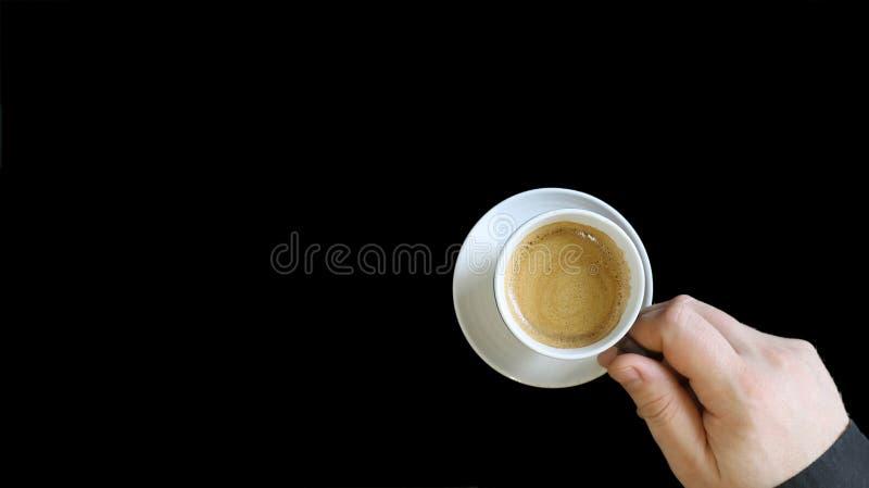 Mano masculina que sostiene una taza de café Ciérrese para arriba de una mano del hombre que sostiene una taza caliente con el ca fotos de archivo