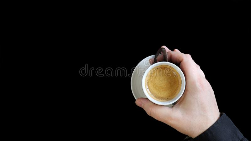 Mano masculina que sostiene una taza de café Ciérrese para arriba de una mano del hombre que sostiene una taza caliente con el ca imágenes de archivo libres de regalías