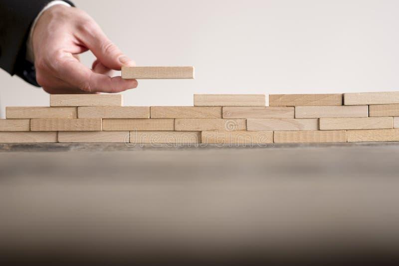 Mano masculina que termina la pared del edificio de ladrillos de madera imagen de archivo libre de regalías