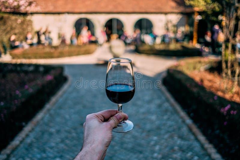 Mano masculina sosteniendo vidrio de Port Wine con bodega y jardín al fondo, en Porto Portugal, ciudad del Port Wine imagen de archivo