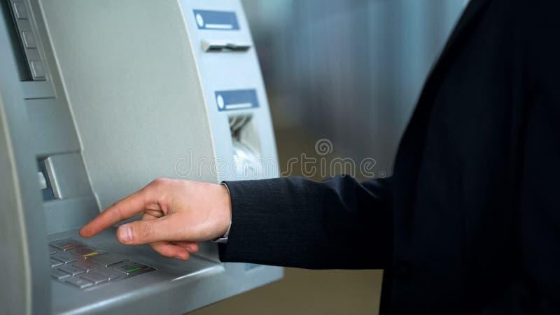 Mano masculina usando cajero automático, código del perno que mecanografía y presionar el botón de la cancelación, error de siste foto de archivo libre de regalías