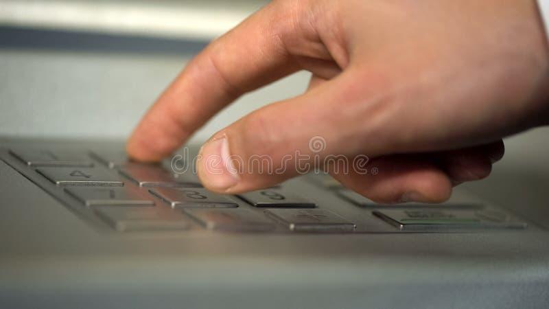Mano masculina usando el cajero automático, insertando código personal único y presionando los botones fotos de archivo