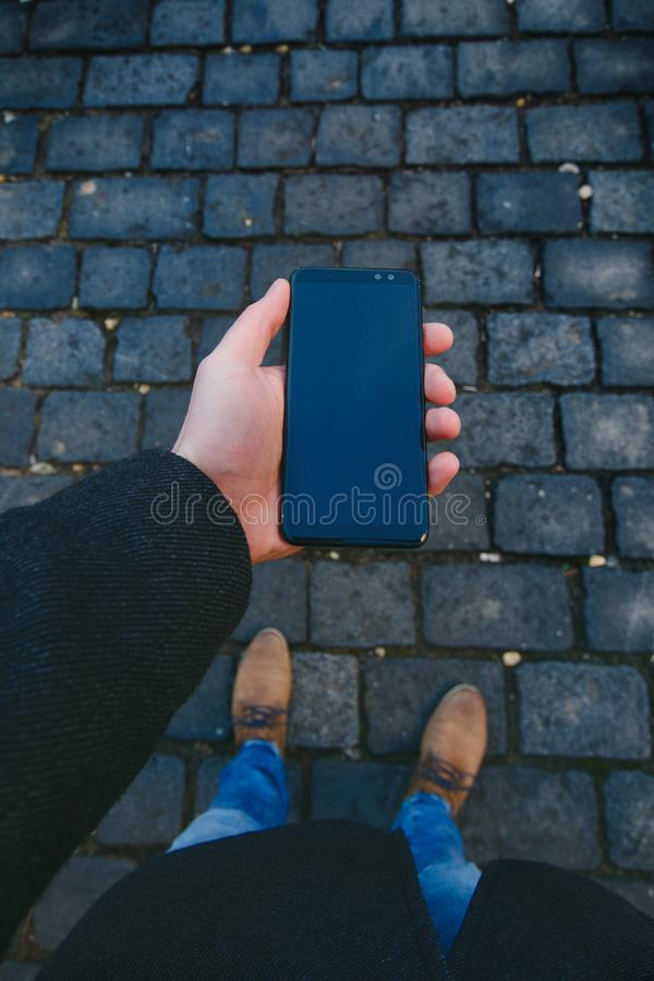 Mano masculina usando el teléfono elegante en la calle Concepto de tecnología y de red social Hombre de negocios con los relojes, foto de archivo libre de regalías