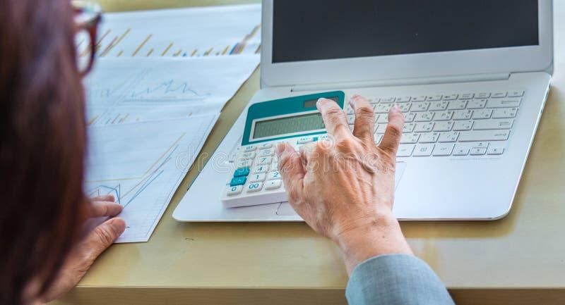 mano mayor de la mujer del primer que trabaja en la calculadora con el ordenador portátil y foto de archivo