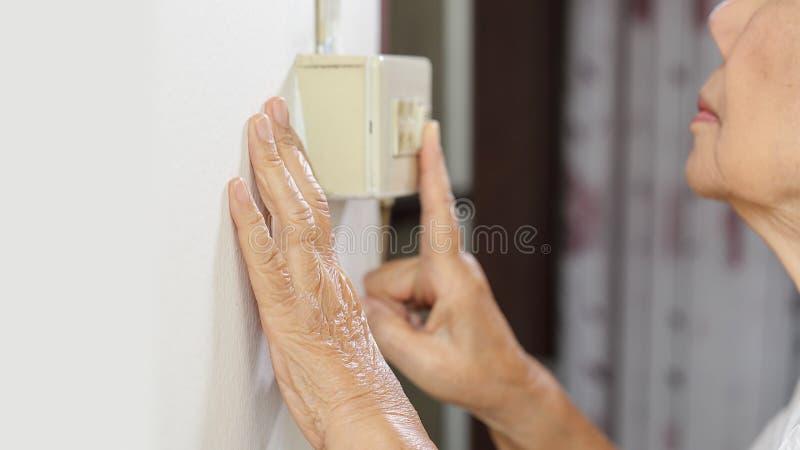 Mano mayor de la mujer que gira un interruptor de la pared foto de archivo