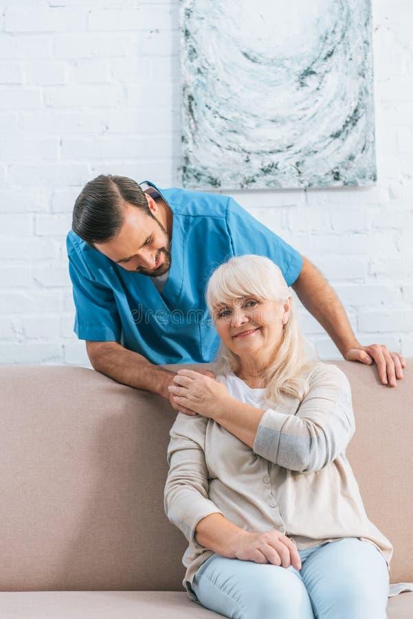 mano mayor feliz de la tenencia de la mujer de la enfermera de sexo masculino joven y de la sonrisa imágenes de archivo libres de regalías