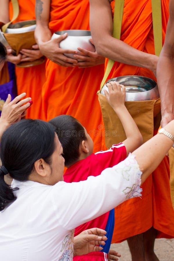 Mano mientras que ruedan las ofrendas puestas de la comida en las limosnas de un monje budista f foto de archivo