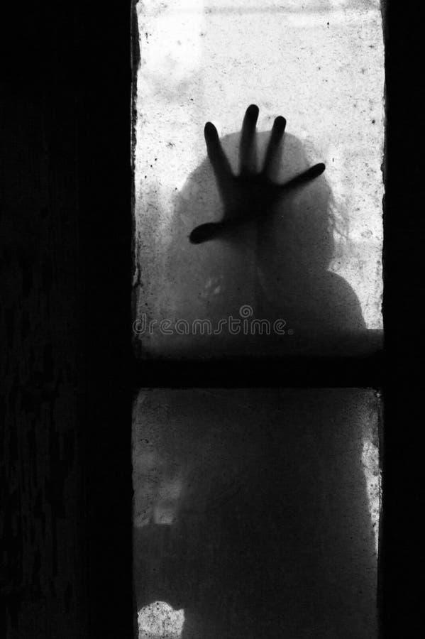 Mano misteriosa su una finestra immagine stock libera da diritti