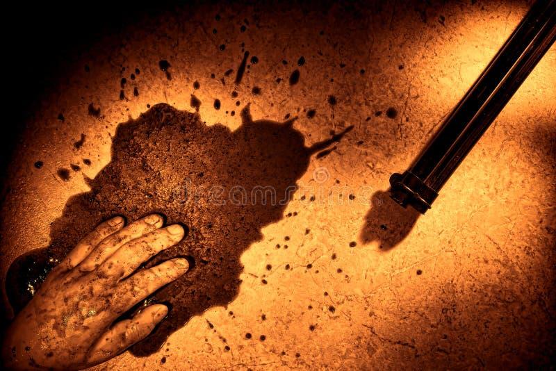 Mano muerta del hombre con la salpicadura de la sangre y el arma del asesinato foto de archivo