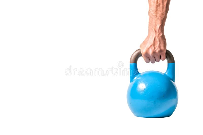Mano muscular fuerte del hombre con los músculos que llevan a cabo el kettlebell pesado azul aislado parcialmente en el fondo bla imagen de archivo libre de regalías