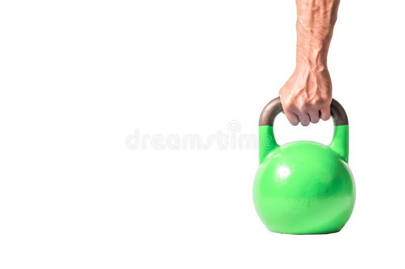 Mano muscular fuerte del hombre con los músculos que llevan a cabo el kettlebell pesado verde aislado parcialmente en el fondo bl foto de archivo