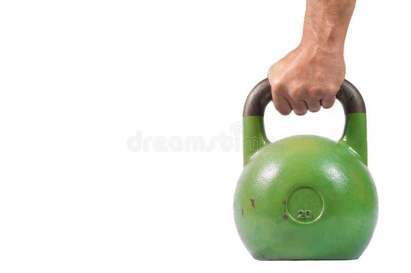 Mano muscular fuerte del hombre con los músculos que llevan a cabo el kettlebell pesado verde aislado parcialmente en el fondo bl imagen de archivo