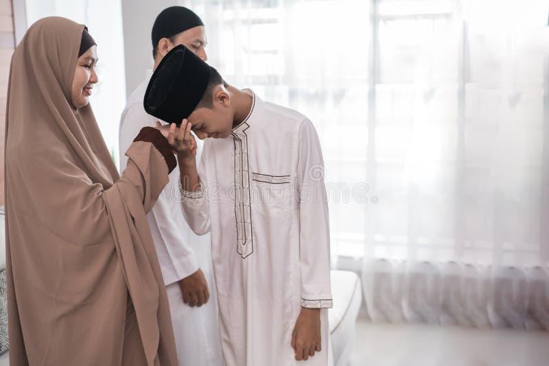 Mano musulm?n asi?tica de la sacudida del padre en el eid Mubarak del fitri del idul imágenes de archivo libres de regalías