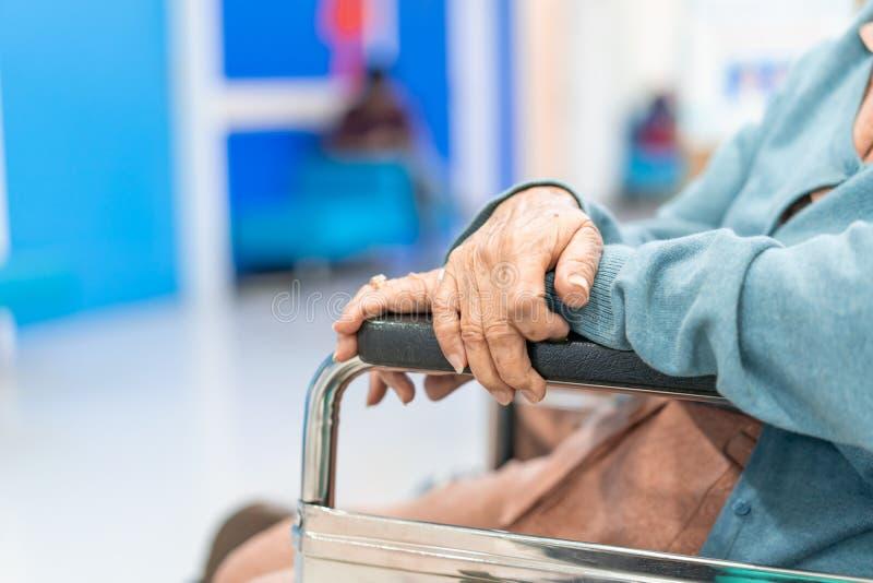 Mano paciente de la mujer de la anciano del primer en la silla de ruedas foto de archivo libre de regalías