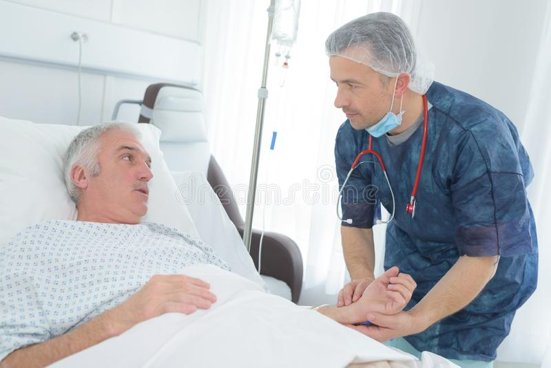Mano paziente della tenuta maschio amichevole di medico nella stanza di ospedale fotografia stock libera da diritti