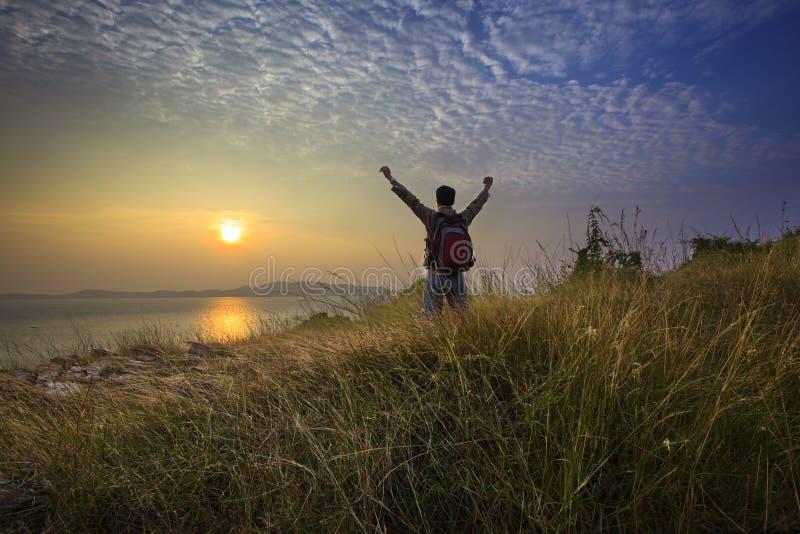 Mano permanente y de levantamiento del hombre joven como victoria en la colina de la hierba que mira al sol sobre el mar horizonta imagen de archivo libre de regalías