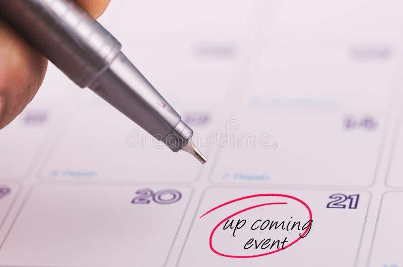 Mano potata che tiene EVENTO IMMINENTE grigio di parola e della penna scritto sul calendario fotografie stock libere da diritti