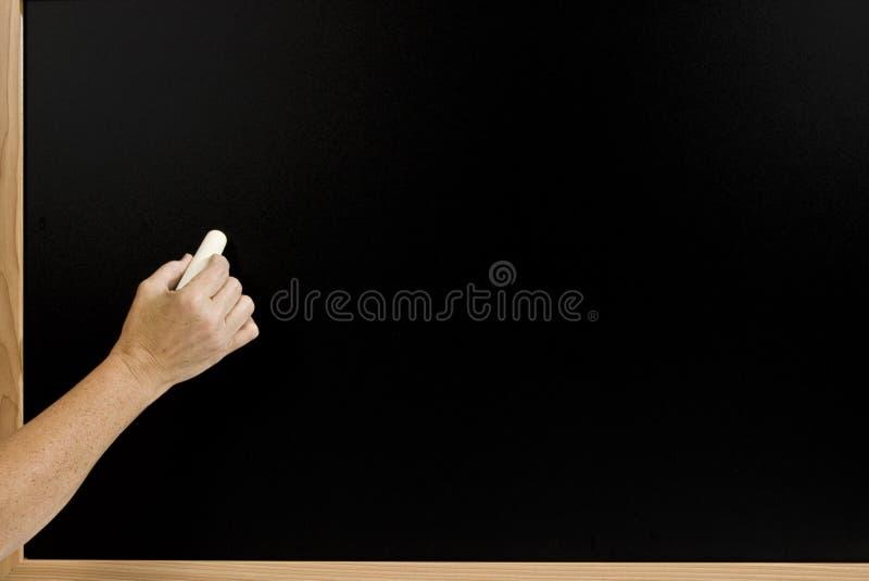 Mano pronta a scrivere sul bordo di gesso in bianco 2 immagine stock