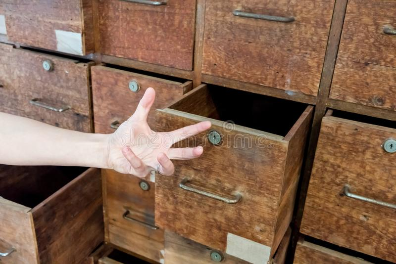 Mano psiquiátrica que abre un cajón del gabinete de madera frecuentado viejo fotos de archivo
