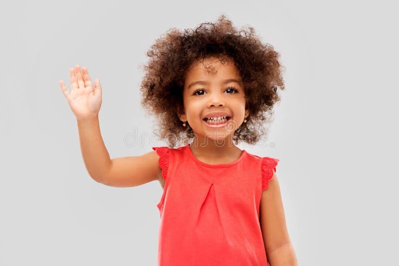 Mano que agita de la peque?a muchacha afroamericana feliz fotos de archivo
