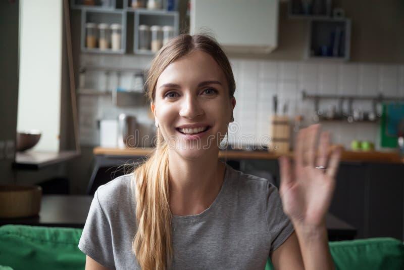Mano que agita sonriente feliz de la mujer del retrato, mirando la cámara imagenes de archivo