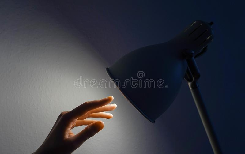 Mano que alcanza para una lámpara imagen de archivo
