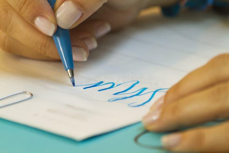 Mano que aprende las letras en clase con la pluma azul y el Libro Blanco foto de archivo libre de regalías