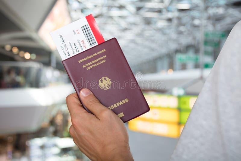 Mano que celebra el pasaporte y el documento de embarque foto de archivo