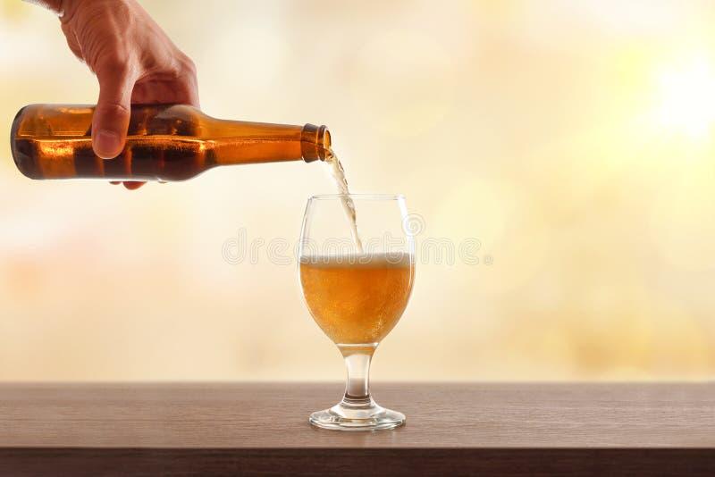 Mano que celebra embotellado de la cerveza un fondo de oro de la taza de cristal foto de archivo