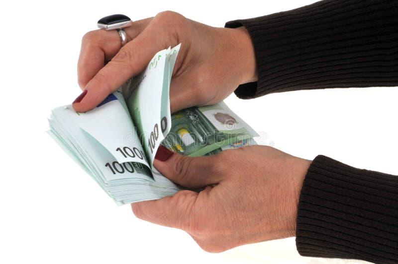 Mano que cuenta un taco de las cuentas de cientos euros foto de archivo libre de regalías