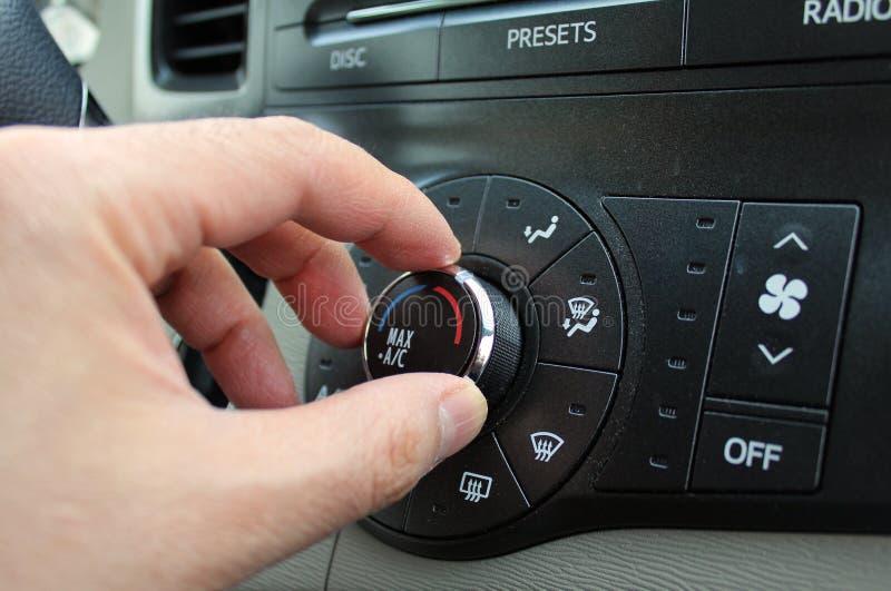 Mano que da vuelta a un botón del calentador del aire acondicionado del coche foto de archivo
