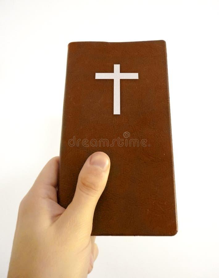 Mano que detiene a Christian Book fotografía de archivo