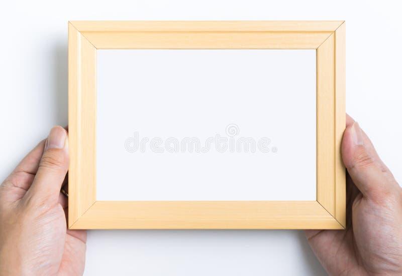 Mano que detiene mofa vacía del marco de la foto foto de archivo