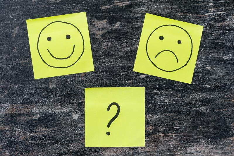 Mano que dibuja smiley infelices y felices Opción, signo de interrogación fotos de archivo
