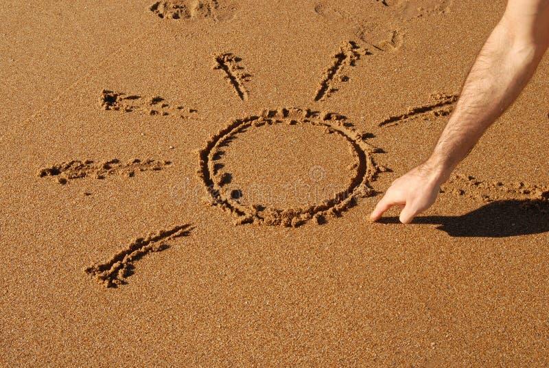 Mano que drena un sol en la arena imagen de archivo libre de regalías