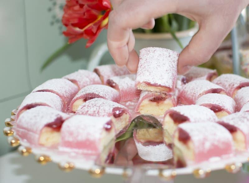 Mano que escoge el pedazo de torta de cumpleaños rosada imagenes de archivo
