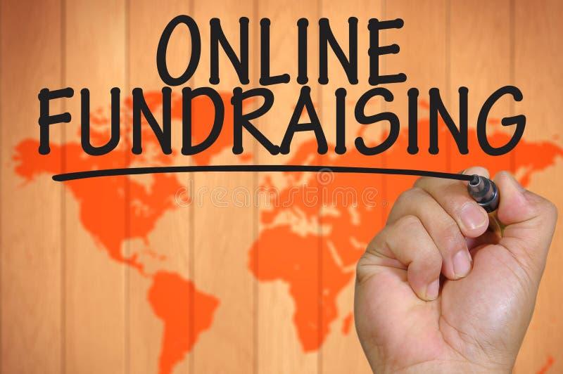 Mano que escribe en línea fundraising imagen de archivo libre de regalías