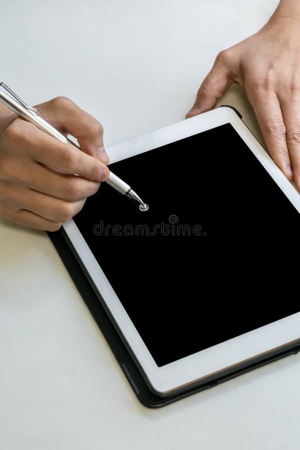 Mano que escribe la pluma digital en la tableta digital en la tabla blanca imágenes de archivo libres de regalías