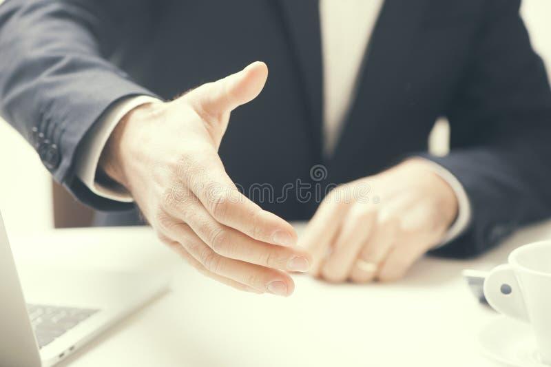 Mano que extiende del hombre de negocios a la sacudida foto de archivo libre de regalías