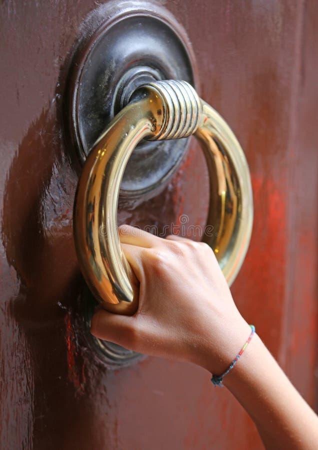 mano que golpea en el a puerta cerrada imagen de archivo